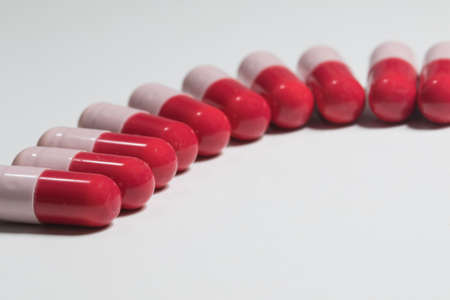 pharmacologist: Group of red and pink antibiotic capsule on white Stock Photo