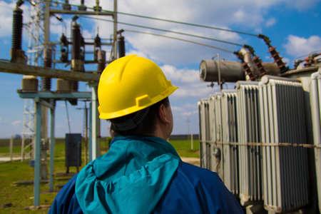 Il tecnico con il casco giallo ispeziona la centrale elettrica ad alta tensione