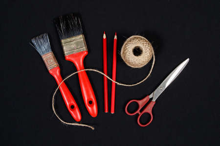 crayon  scissors: Packthread  two red  paint  brushes  crayons and   scissors on black background