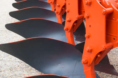 Detail of orange plough for a Farming Tractor Stock Photo