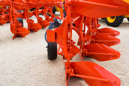 plough: Detail of orange plough for a Farming Tractor Stock Photo