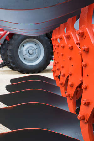 plough: Detail of orange plough for a Farming Tractor and wheel