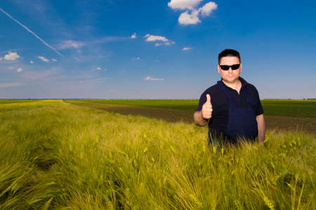dirtied: Satisfied farmer in the wheat field on sany day Stock Photo