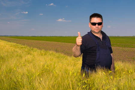 Satisfied farmer in the wheat field on sany day Stock Photo