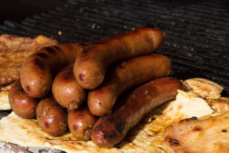 barbequing: Sausages, juicy meat and bread on barbeque
