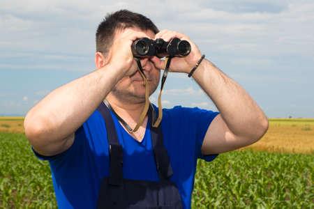 dirtied: Farmer with binoculars observe birds  in the field