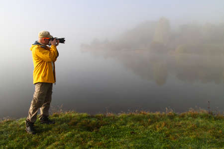 yellow jacket: Nature photographer in yellow jacket in action
