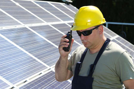 walkie talkie: Green energy, solar panel and worker with walkie talkie