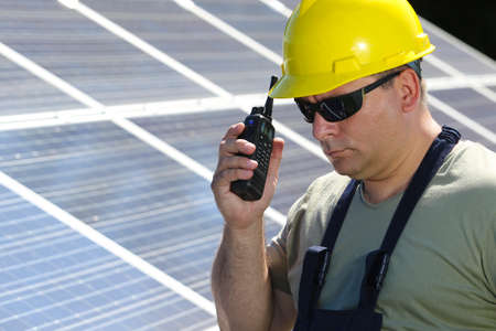 walkie talkie: Engineer is make call with a  walkie talkie in solar power plant Stock Photo