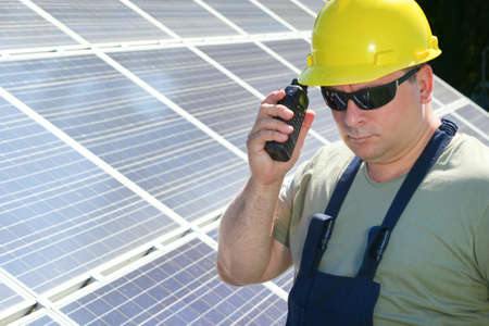 walkie talkie: Green energy, solar panels and worker with walkie talkie Stock Photo