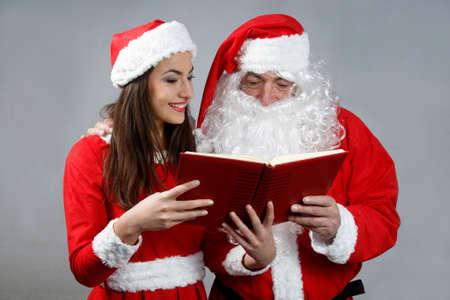 sexy xmas elf: Santa claus and  girl elf  reading wish book