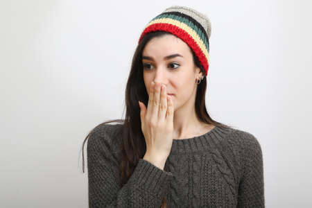Surprised hipster girl with brown pullover and hat