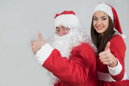 Happy Santa Claus and  girl elf show OK sign