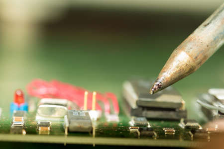 Repair electronic circuit board with soldering iron Stock Photo
