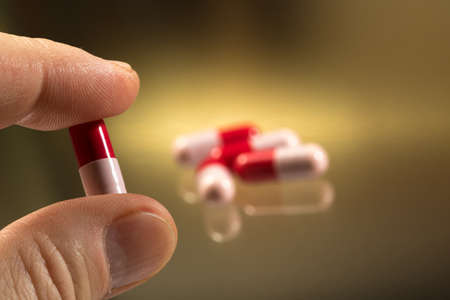 Close up of  antibiotic capsule between the fingers