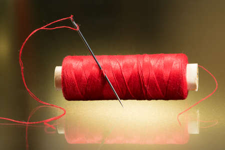 hilo rojo: Needle and red thread on the golden background