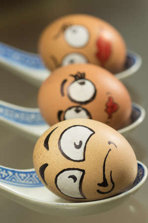 Three frightened egg faces on the porcelain spoons