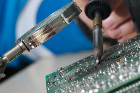 Repair short circuit with a soldering iron and a magnifying glass