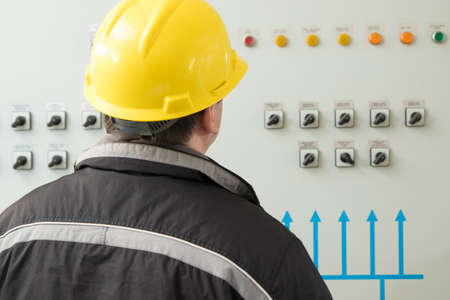 Engineer in yellow helmet reading instruments in power plant control center