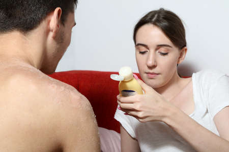 unprotected: Girl is reading instruction for skin care cream after sunburn Stock Photo