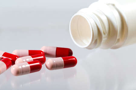 Closeup of Red and pink probiotics capsule and bottle