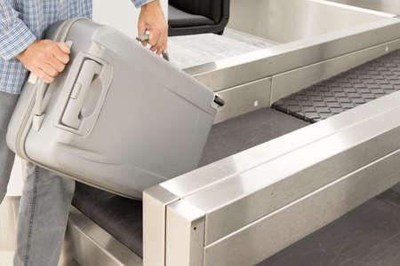 Hombre puso equipaje en el mostrador de facturación en el aeropuerto Foto de archivo - 86501252