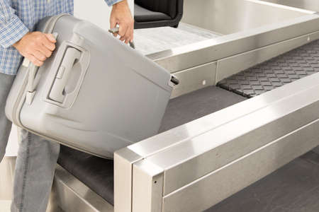 Man put Luggage at check-in counter at airport