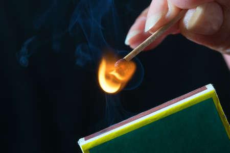 Vrouw slaan een wedstrijd op en maak een vuur aan Stockfoto
