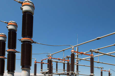 Power plant detail,  red high voltage isolation on blue sky