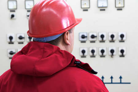 dispatcher: Technician with red  helmet reading instruments in power plant control center