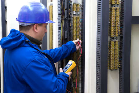 Worker in blue helmet make electrical measurements