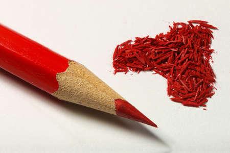 白い紙に鉛筆と赤いグラフィット鉛筆から赤いハート形の破片