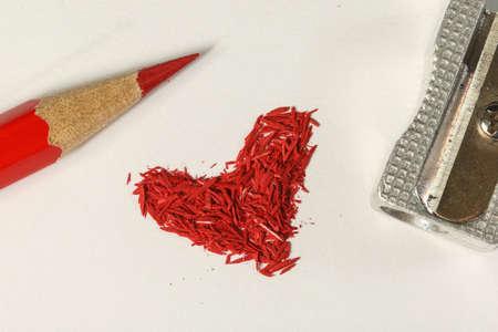 白い紙に鉛筆シャープと赤いグラフィット鉛筆から赤いハート形の破片 写真素材