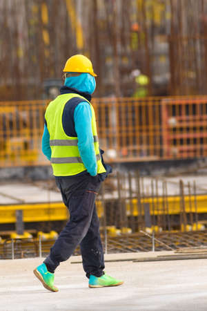 Twiddler is walking with hands in pockets through the  construction site Stock Photo