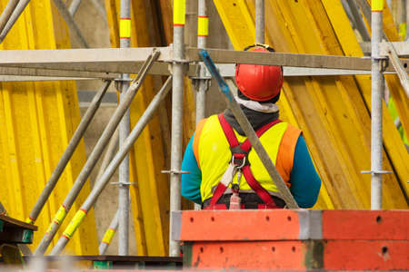 Worker in red helmet standing opposite of yellow scaffolding in reconstruction area