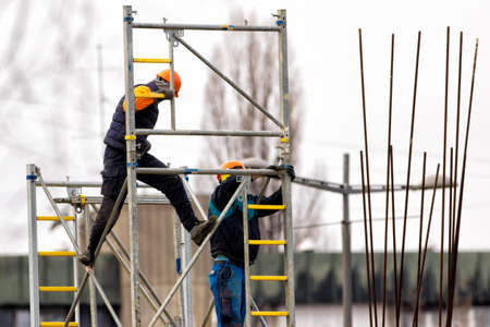 Two builders  build metal scaffolding on construction site Foto de archivo