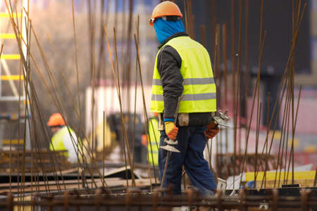 Builder in orange helmet transfers the reinforcement at the construction site
