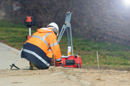 Surveyor worker in orange  perform geodetic measurement Stock fotó