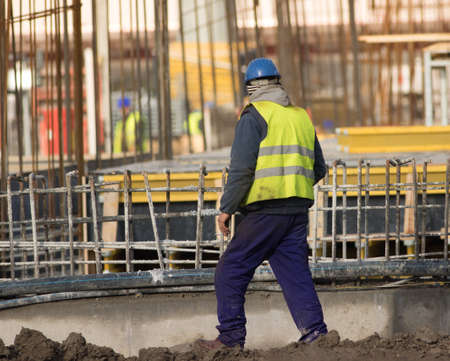 Lazy worker is walking with  cigarettes through the  construction site