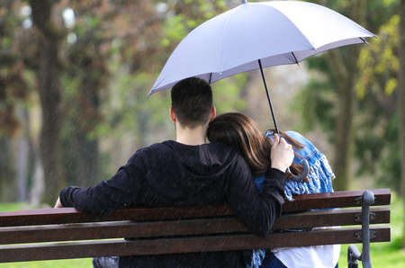 Rainy day boy and girl sitting on bench  with umbrella Stock Photo