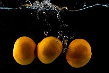 Three ripe clementines in water splash on black background