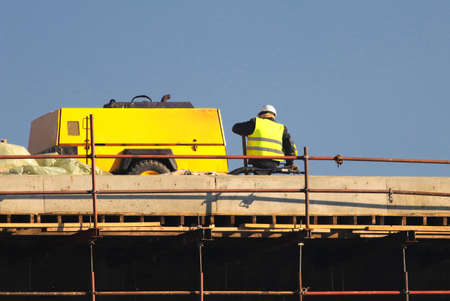Worker in yellow at the construction site ower blue sky