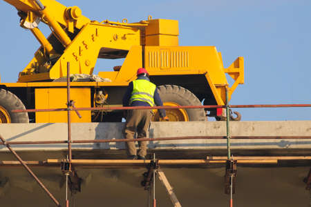 Worker in yellow and crane at the construction site