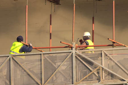 Two builders in yellow at the reconstruction area work on scaffolding