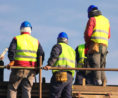 Workers in yellow and blue helmet on the reconstruction area