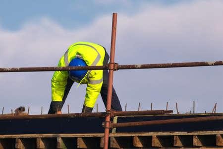 Worker with blue helmet knitting metal rods bars into framework reinforcement Banque d'images