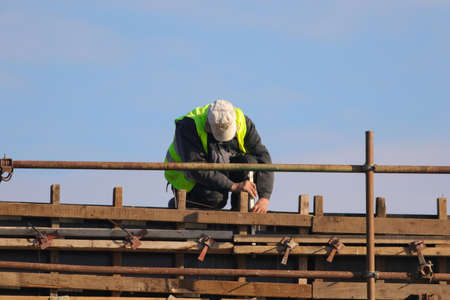 Builder knitting metal rods bars into framework reinforcement Banque d'images