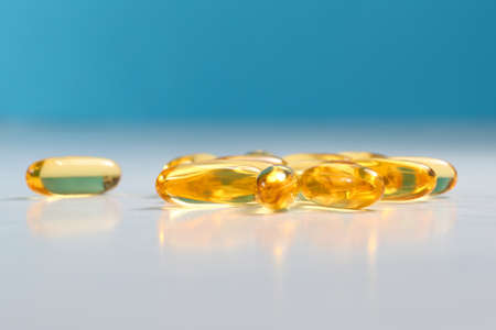 Yellow fish oil capsules, omega 3 on white and blue background Stockfoto