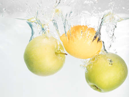 Two apples and lemon splash in water on white