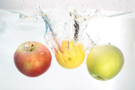 Two apples and lemon splash in water on white background